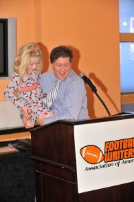 Jon Wilner, with the acrobatic help of his daughter Anna, accepted the FWAA's Beat Writer of the Year Award. (Photo courtesy of Rose Bowl)