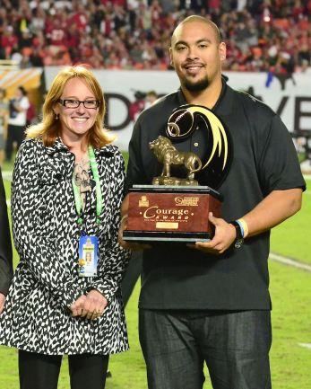 FWAA member Andrea Adelson of ESPN.com presents the 2013 Discover Orange Bowl/FWAA Courage Award to winner Anthony Larceval of San Jose State on the field during the 2014 bowl game. (Photo courtesy of the Discover Orange Bowl)