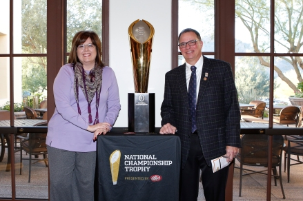2015 FWAA President Lee Barfknecht and his wife, Sara, pose with the CFP national championship trophy at the FWAA's annual Awards Breakfast on Jan. 11, 2016, in Scottsdale, Ariz. Photo by Melissa Macatee.