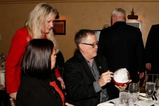 Former FWAA President Chris Dufresne signs a football as Margaret Mason (standing) and Dufresne's wife, Sheila, look on. Photo by Melissa Macatee.