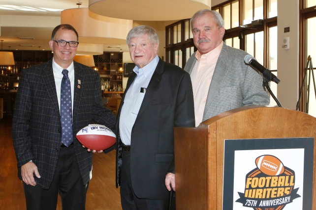 Irv Moss of the Denver Post, center, receives a commemorative football in recognition of his Lifetime Achievement Award from 2015 FWAA President Lee Barfknecht, left, and Tim Simmons of BFI Events, right.  Photo by Melissa Macatee for the FWAA.