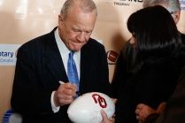 Former Oklahoma Coach Barry Switzer, winner of this year's Tom Osborne Legacy Award, autographs a football for a fan at the Outland Trophy Presentation Banquet on Jan. 11, 2017, in Omaha. Photo by C41 Photography.