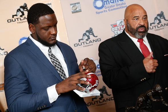 2016 Outland Trophy winner Cam Robinson of Alabama autographs a mini-helmet while Greg Roberts of Oklahoma, the winner of the trophy in 1978, looks on. Roberts received his Outland Trophy on the same night as Robinson. Photo by C41 Photography.