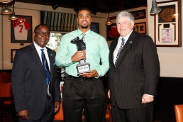 Armed Forces Merit Award winner Steven Rhodes, a former Marine and defensive end at Middle Tennessee State, is flanked by Dr. Sidney A. McPhee, president of Middle Tennessee State (left) and Athletic Director Chris Massaro at the FWAA's Awards Breakfast on Jan. 9, 2017, in Tampa. Photo by Melissa Macatee.