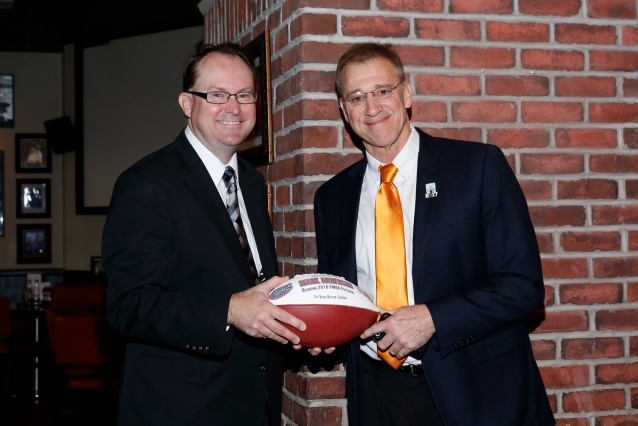 Outgoing FWAA President Mark Anderson (left) receives a commemorative football in recognition of his service to the organization from incoming President Dave Jones of PA Media Group. Photo by Melissa Macatee.