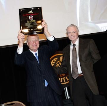 Former Oklahoma Coach Barry Switzer, with former Nebraska Coach Tom Osborne, hoists his Tom Osborne Legacy Award during the Outland Trophy Presentation Banquet on Jan. 11, 2017, in Omaha. Photo by C41 Photography.