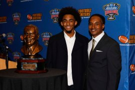 Eddie Robinson IV (left) and Eddie Robinson III (right) pose with the FWAA Eddie Robinson Coach of the Year Bust. (Photo by Melissa Macatee)