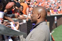 Former Alabama and NFL running back Shaun Alexander, namesake of the Shaun Alexander/FWAA Freshman of the Year Award, signs autographs along the sideline at Clemson's 2019 spring game. He was there to honor the award's inaugural recipient, Clemson quarterback Trevor Lawrence. Photo by Shane Sandefur.