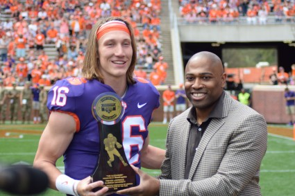 Former Alabama and NFL running back Shaun Alexander presents the inaugural Shaun Alexander/FWAA Freshman of the Year Trophy to Clemson quarterback Trevor Lawrence. The formal presentation occurred at Cloemson's 2019 spring game. Photo by Shane Sandefur.