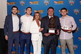 LSU Coach Ed Orgeron with the FWAA/Eddie Robinson Coach of the Year Award and his wife and sons. (Photo by Melissa Macatee)