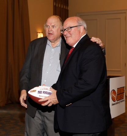 Paul Hoolahan of the Allstate Sugar Bowl (right) receives a commemorative football signifying his FWAA Lifetime Achievement Award from FWAA member Ted Lewis. (Photo by Melissa Macatee)