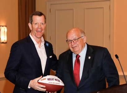 Past president Ivan Maisel (left) presents a commemorative football signifying the FWAA's Lifetime Achievement Award to Wright Waters of the Football Bowl Association. (Photo by Melissa Macatee)